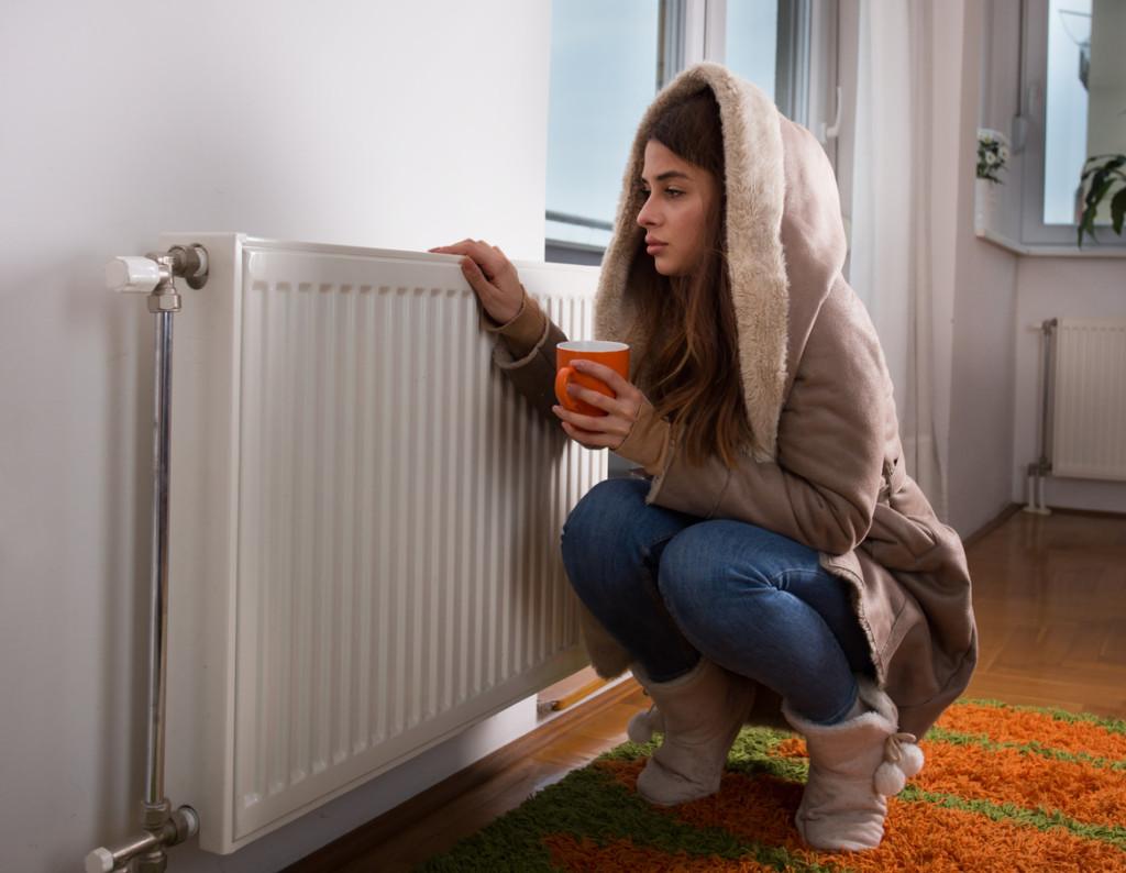 Wychłodzone mieszkanie w okresie zimowym. Kobieta grzeje się przy kaloryferze