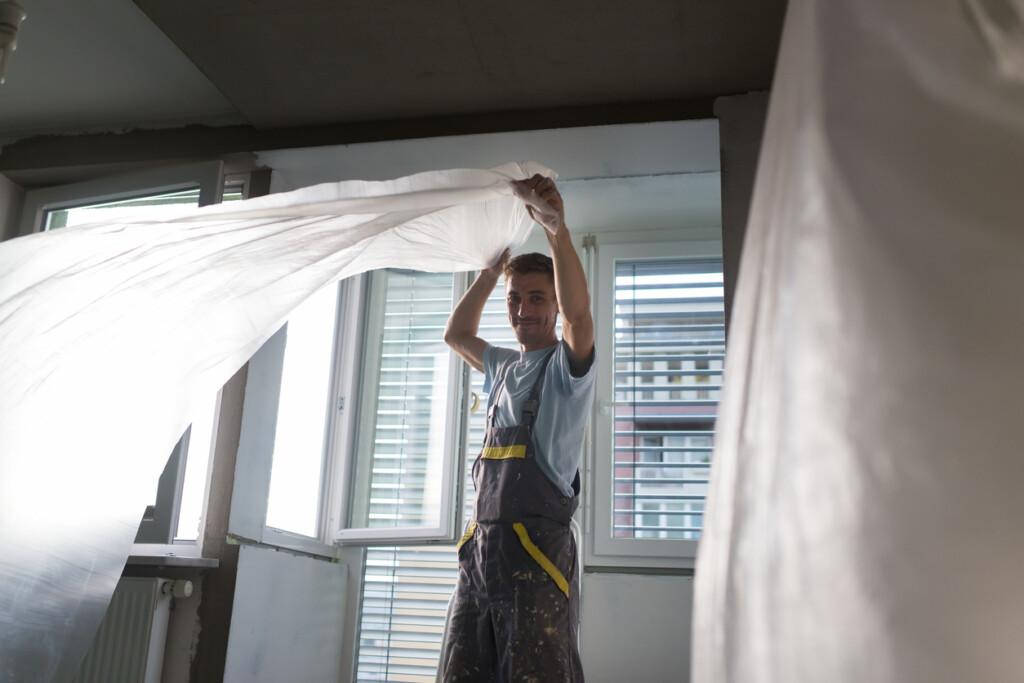 Robotnik zabezpiecza folią mieszkanie podczas remontu.