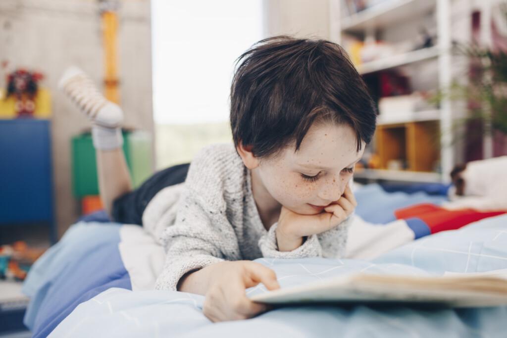 Chłopiec czytający książkę nałóżku.