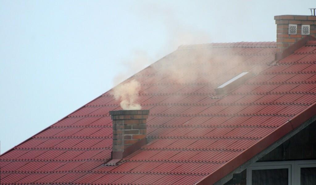Dym unoszący się zkomina domu jednorodzinnego.
