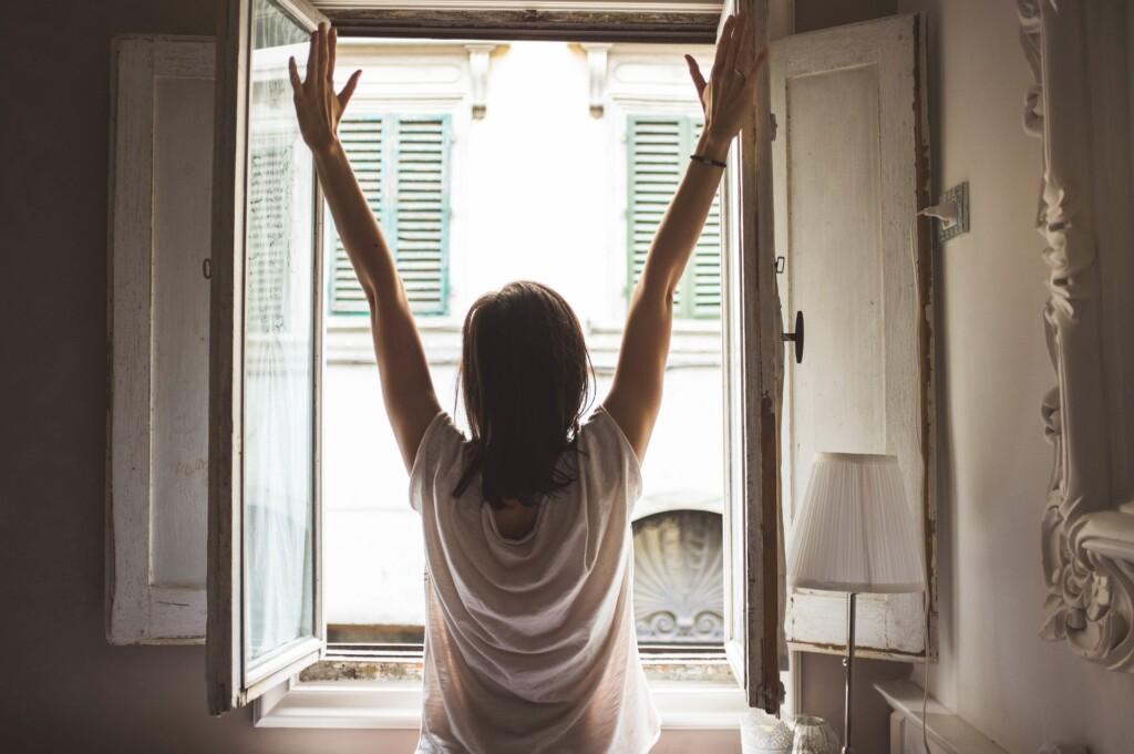 Kobieta stojąca wotwartym oknie.